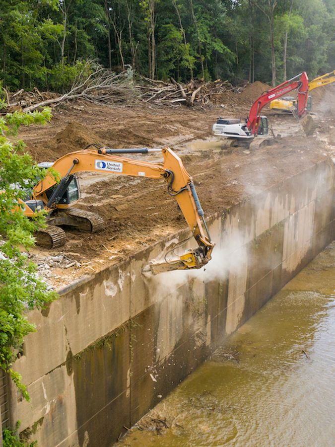 Construction equipment at work dismantling a dam.