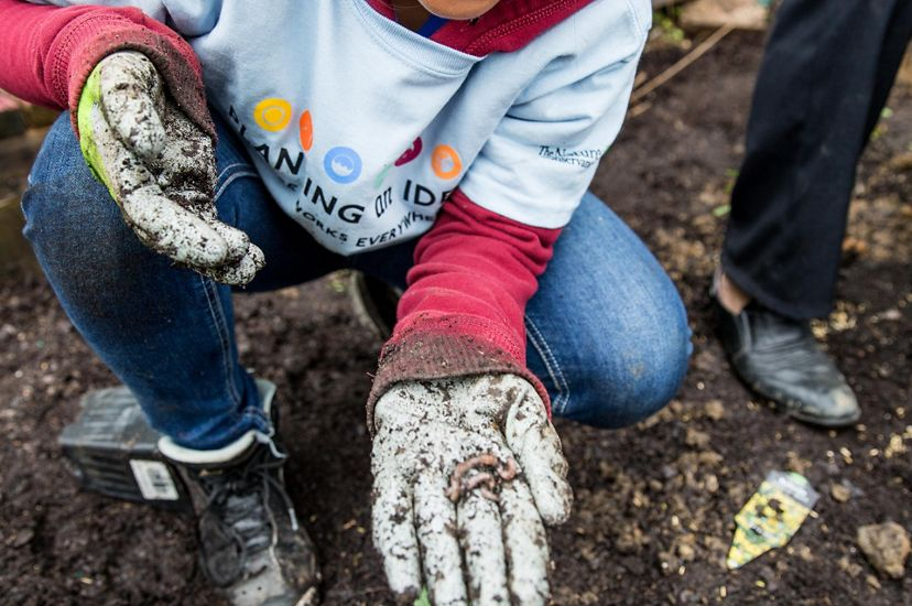 A child crouches in the dirt at a school garden. She holds her gloved hand out to show a small earthworm curled up in her palm.