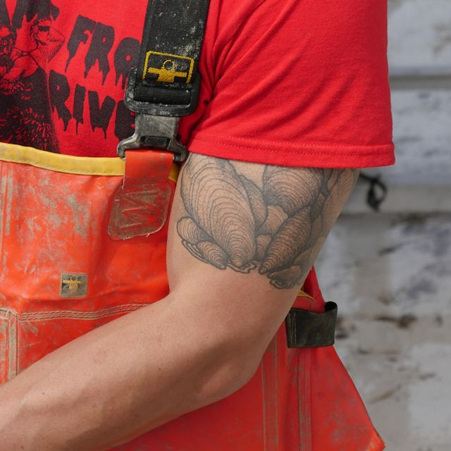 Cropped view of a man shucking an oyster. He is wearing orange overalls. A large oyster tattoo is visible on his bicep.