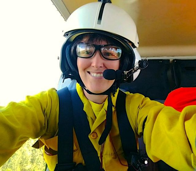 Candid portrait of Restoration Coordinator Nikole Simmons taken in a helicopter. A smiling woman wearing a white helmet and yellow fire gear. Her arms are outstretched taking a selfie.