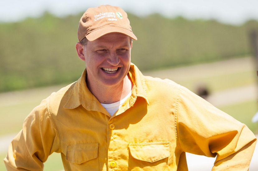 Candid portrait of Virginia Pinelands Program Director Brian Van Eerden. A smiling man wearing a brown cap and yellow fire gear stands on the open runway of a small airport.