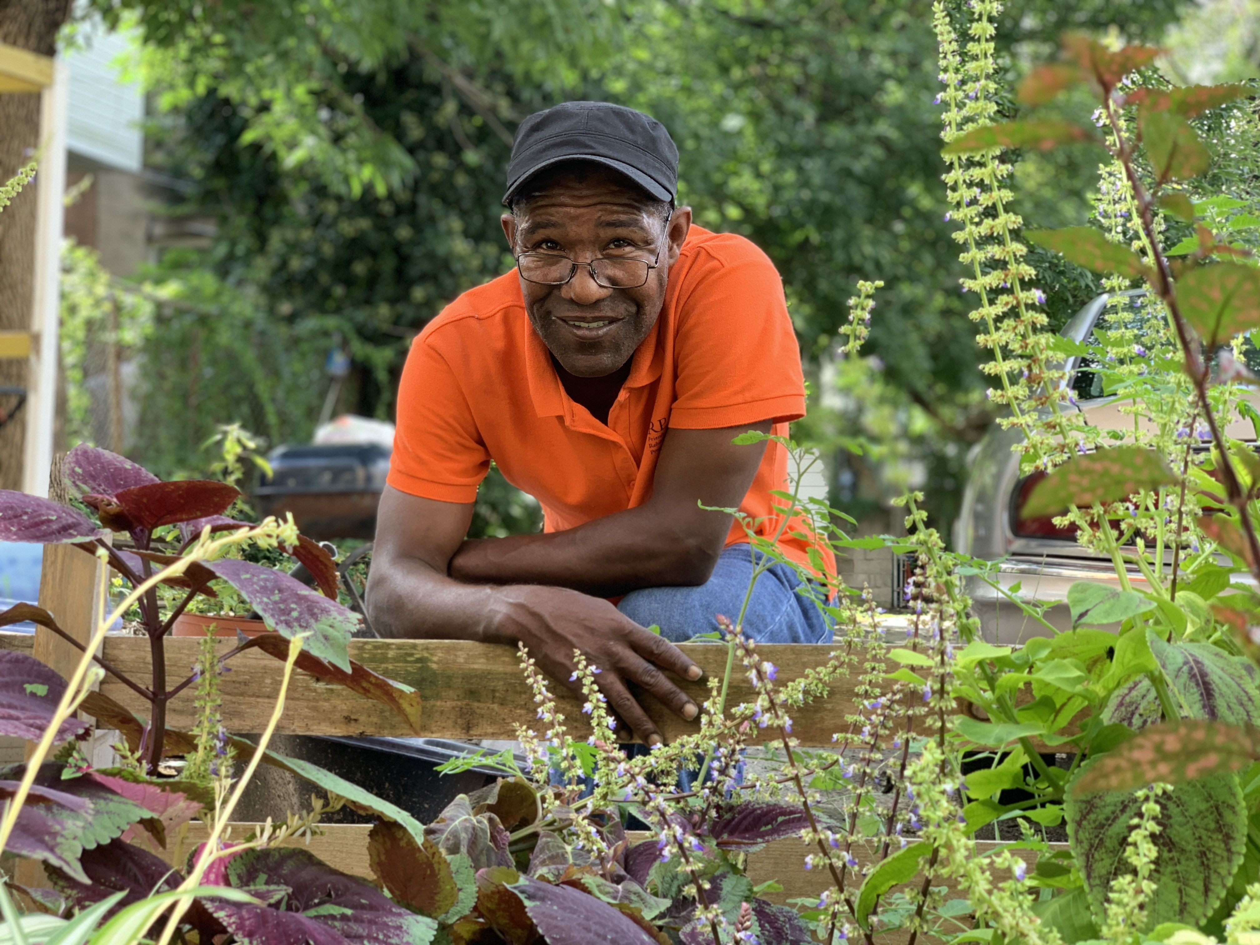 a man stands in front of a neighborhood garden