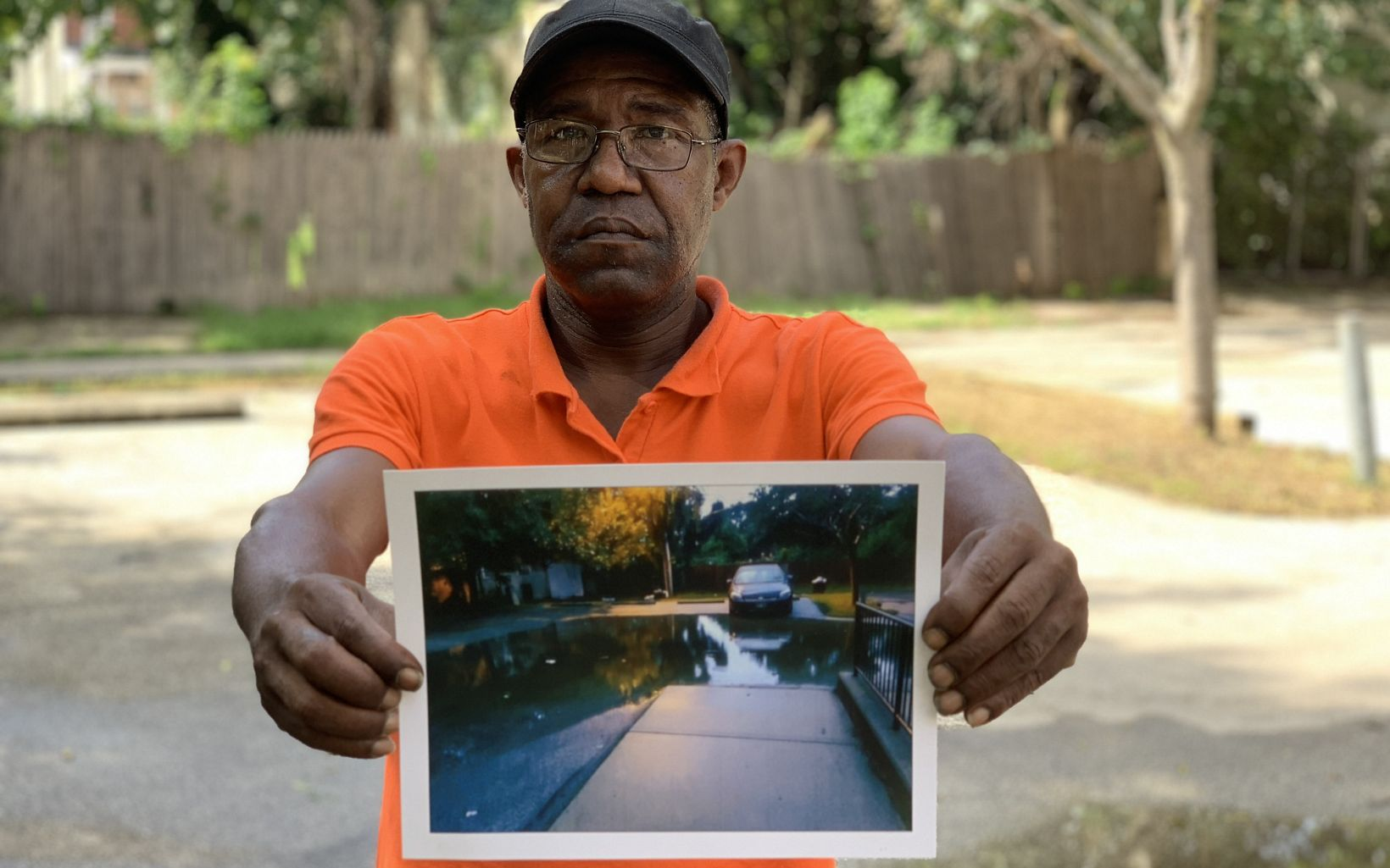 a man standing in the middle of a parking lot holds a photo of the parking flooded