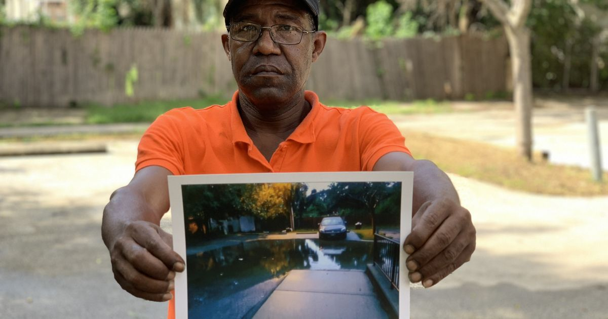 a man holds a picture of a flooded street