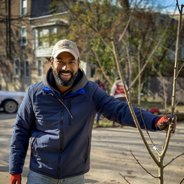 A smiling man stands next to a newly planted tree.