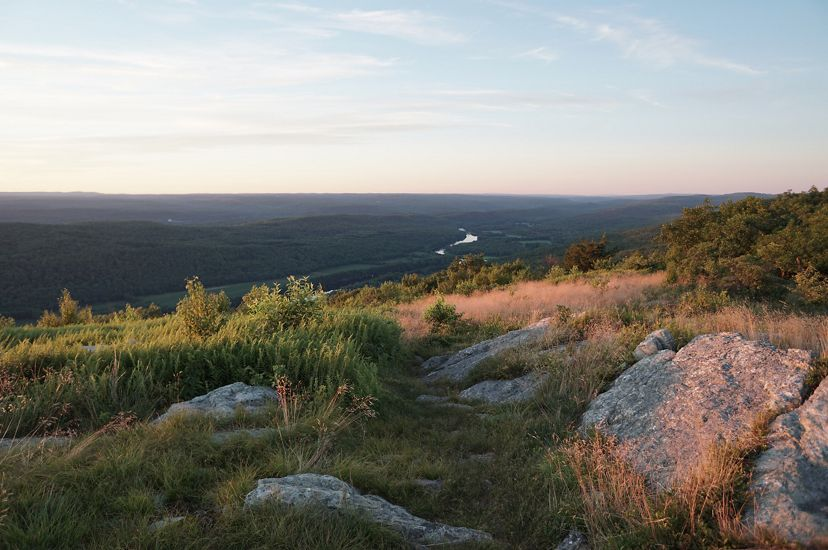 Green forested mountain ridges and valley stretch out to the horizon as the sun rises on the Appalachian Trail.