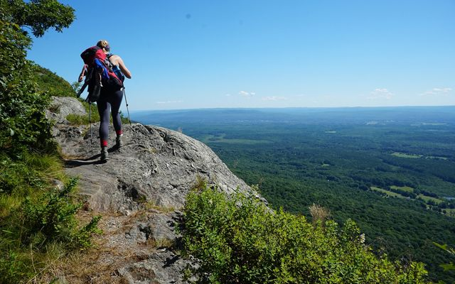 A woman carrying a heavy pack hikes up a trail cut into mountain rock. A wide forested valley spreads out far below her.