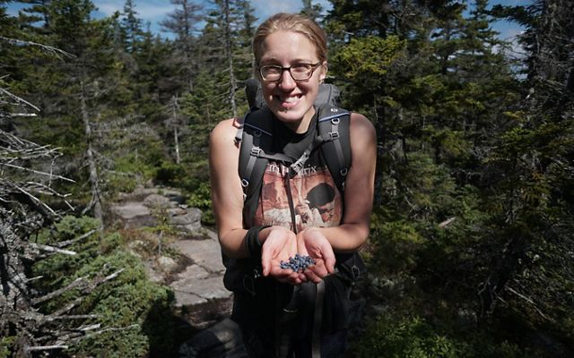A smiling woman holds freshly picked wild blueberries in her cupped hands. She is standing on a trail surrounded by tall trees.