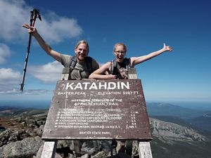 A man and woman stretch out their arms in celebration. They're standing behind a large sign marked KATAHDIN that marks the northern terminus of the Appalachian Trail.