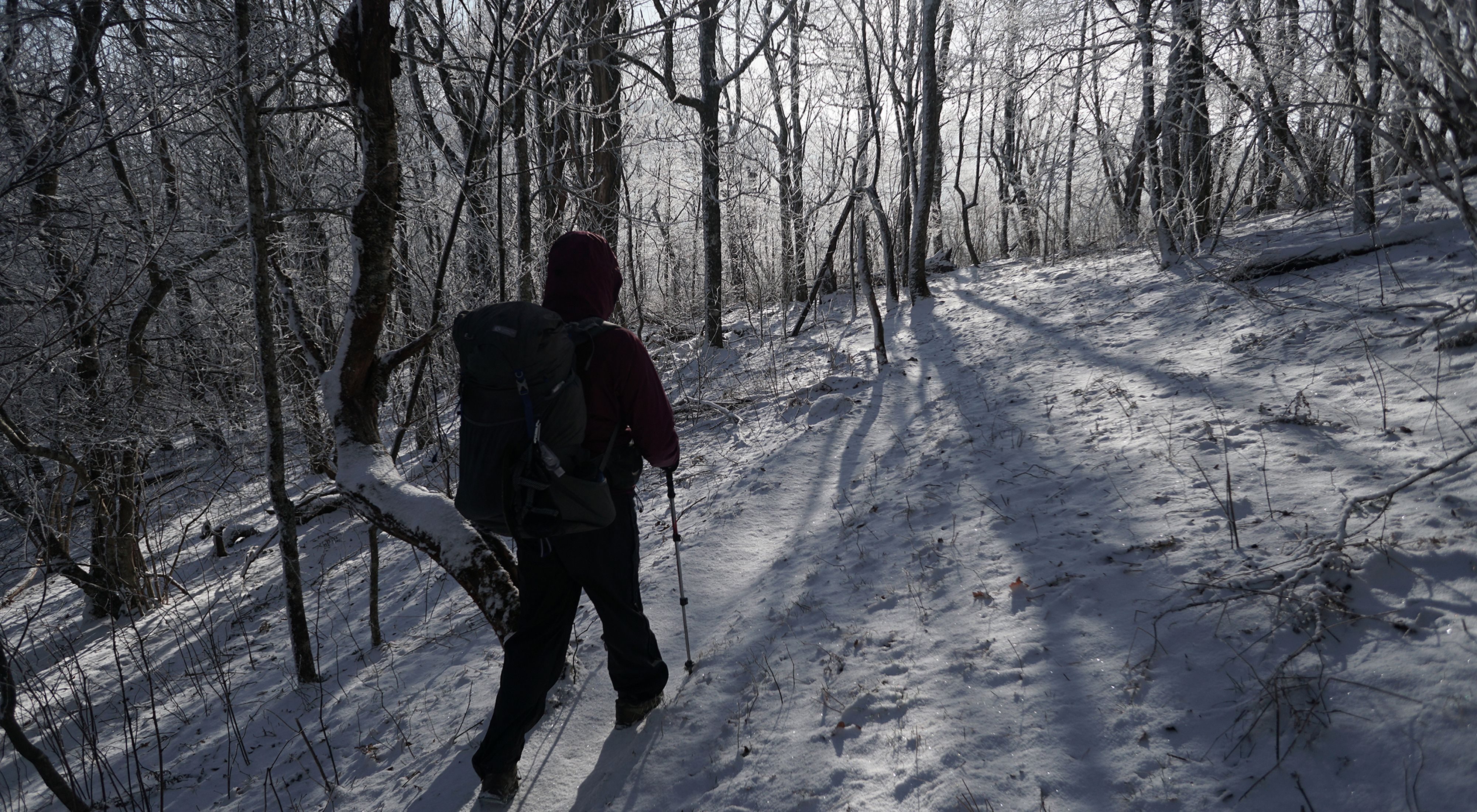 A woman bundled in a heavy parka and carrying a large backpack uses walking sticks to hike a snowy mountain trail.