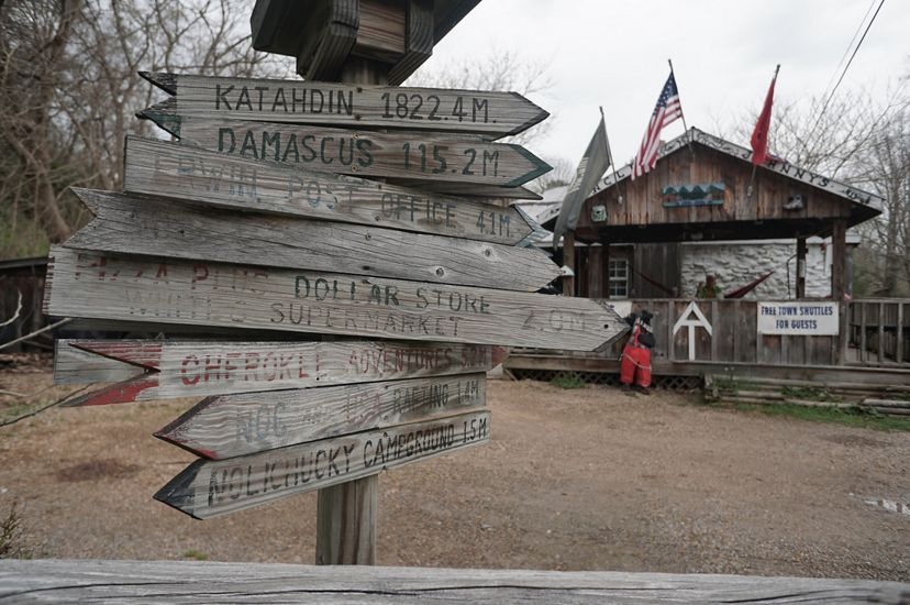 A wooden waypost sign in the foreground show distances to points along the Appalachian Trail. A rustic general store is in the background.
