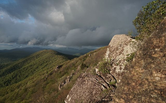 Gray clouds hang heavy and low along a forested mountain ridge line.