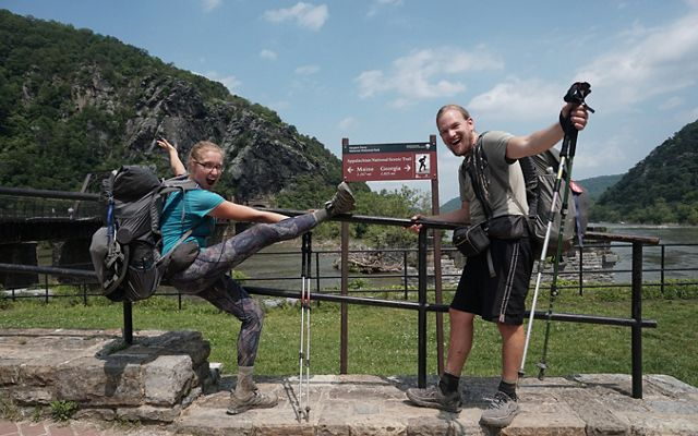 A woman and man celebrate and pose next to a sign marking the midpoint of the Appalachian Trail in Harpers Ferry, WV.