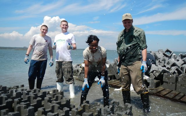 Four volunteers use large interlocking concrete pieces to build oyster castles. Salt spray is kicked up as the waves splash against the blocks.