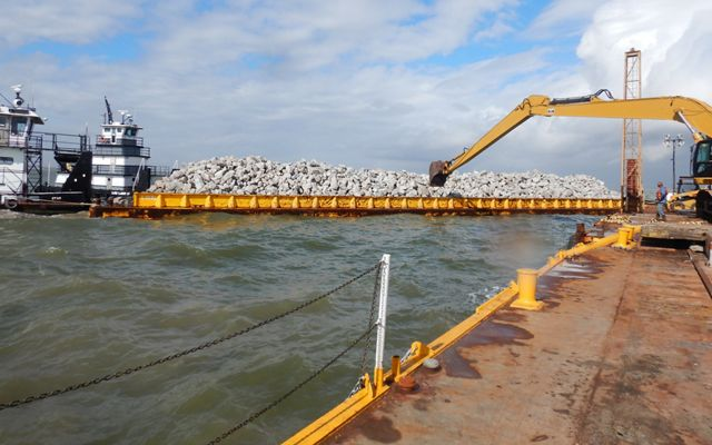 A barge full of limestone boulders to be used for oyster reef construction at Galveston Bay.
