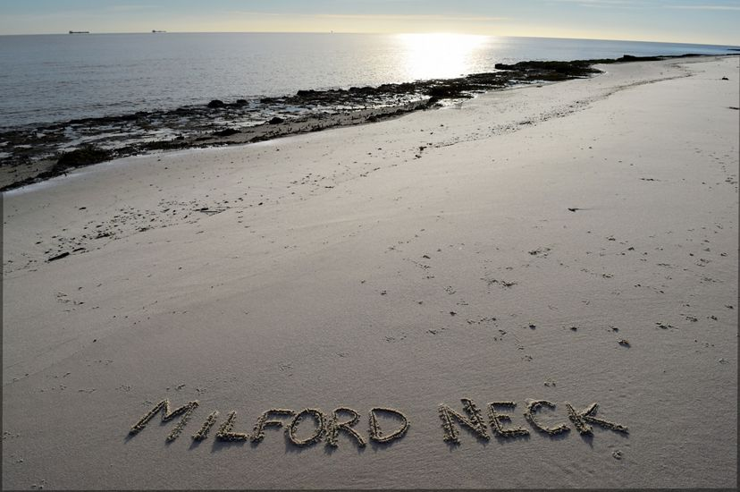 A wide open stretch of beach ends at a shoreline edged with seaweed. The sun reflects on the calm surface of the Delaware Bay. In the foreground the words, Milford Neck, have been written in the sand.