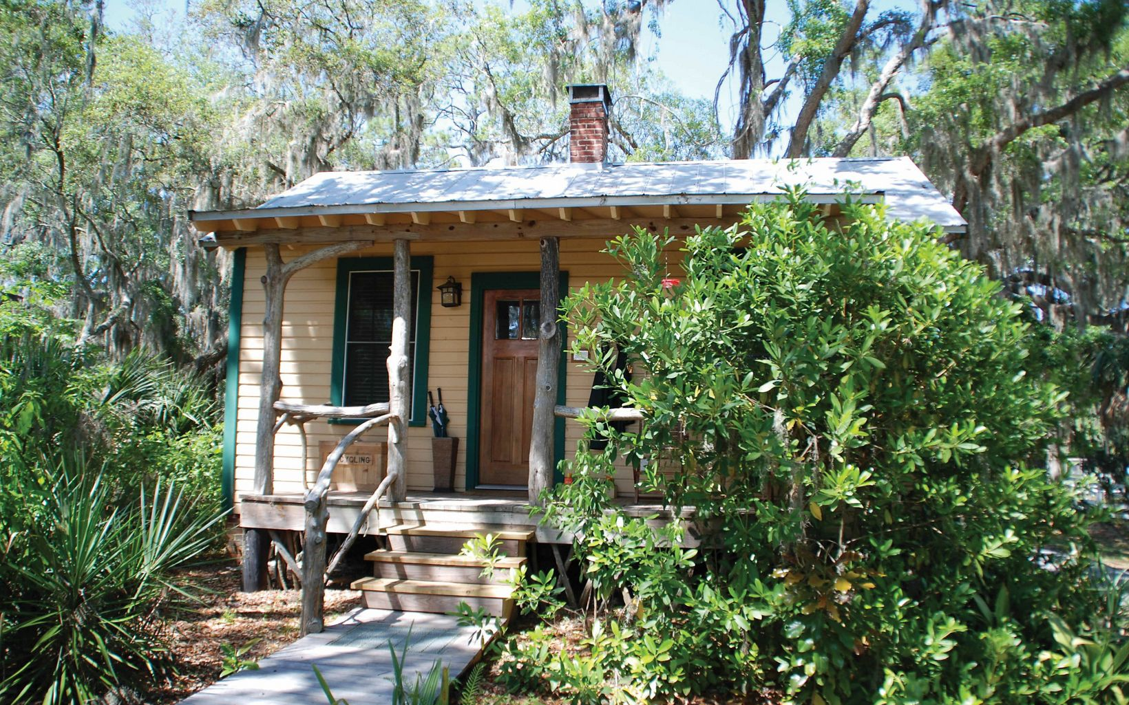 A small cabin accommodation on Little St. Simons Island nestles amongst green grasses and trees draped in spanish moss.