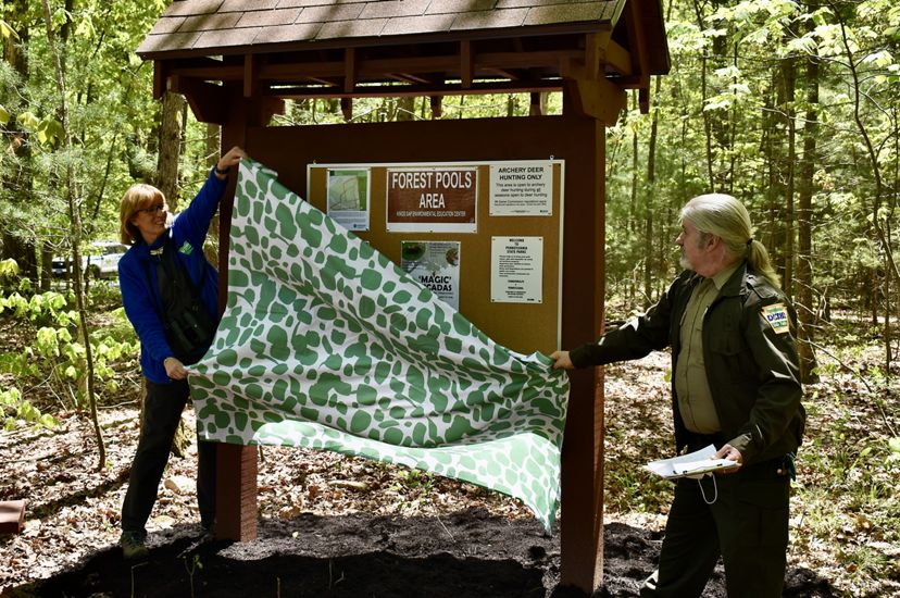 Two people remove a green and white sheet from a new preserve kiosk, part of a land transfer ceremony with the state of Pennsylvania. The kiosk contains signs and visitor information.