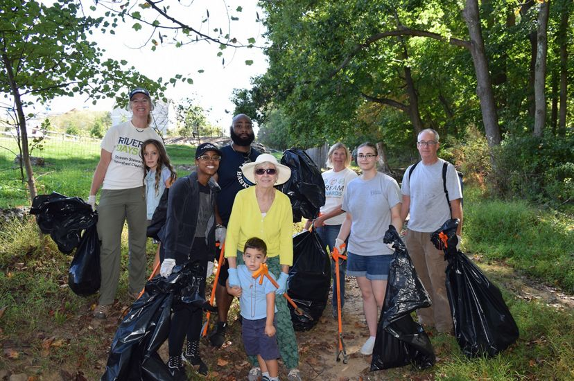 A group of nine people pose together for a photo during a clean up event. The diverse group is holding large black trash bags and bright orange grabbers.