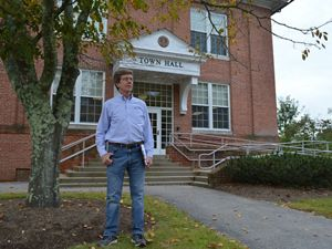 A man stands in front of a town hall building.
