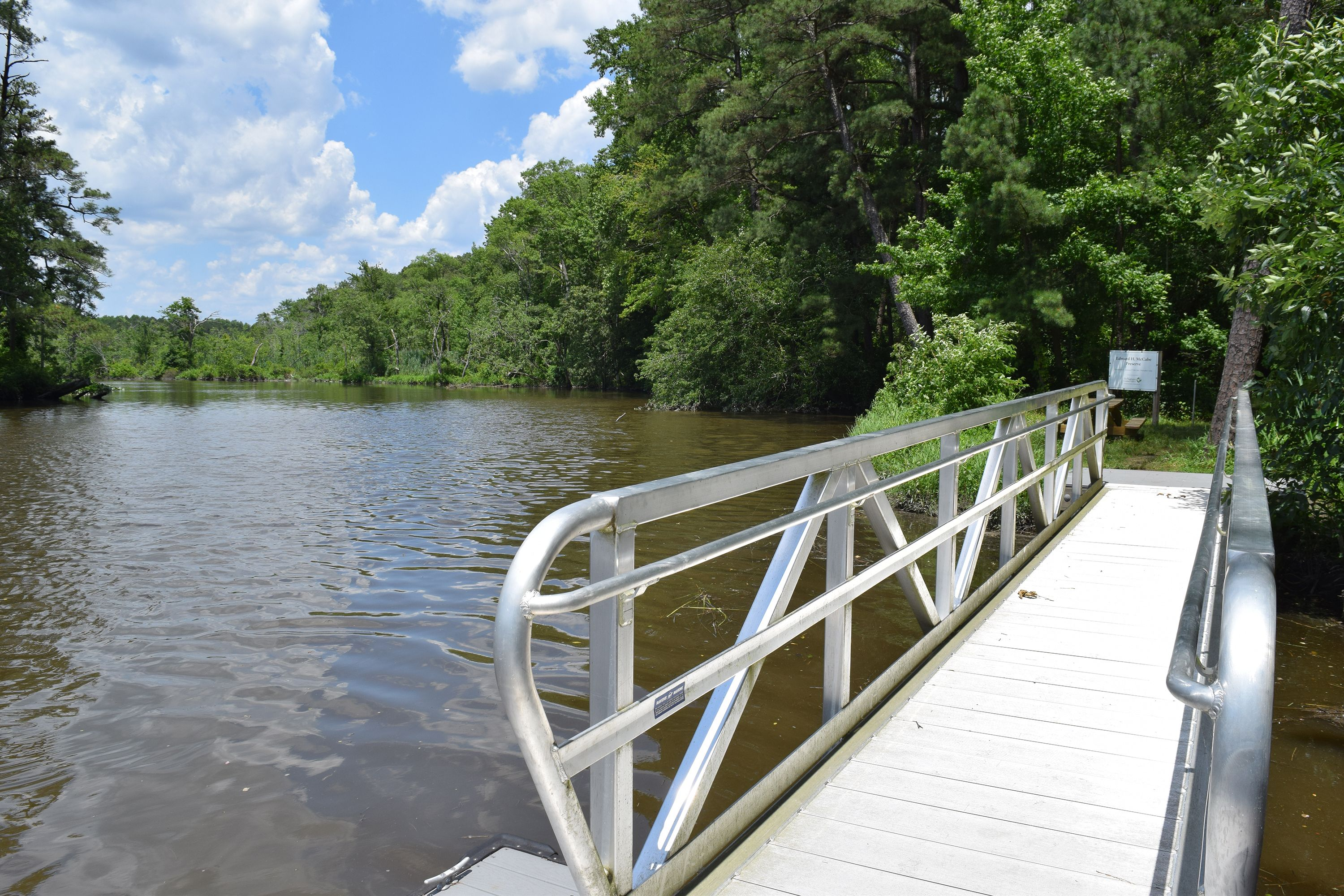 View from the end of a narrow floating dock with high metal sides. The dock leads to a path that disappears into a thick forest. Trees line the banks of the wide river that stretches to the horizon.