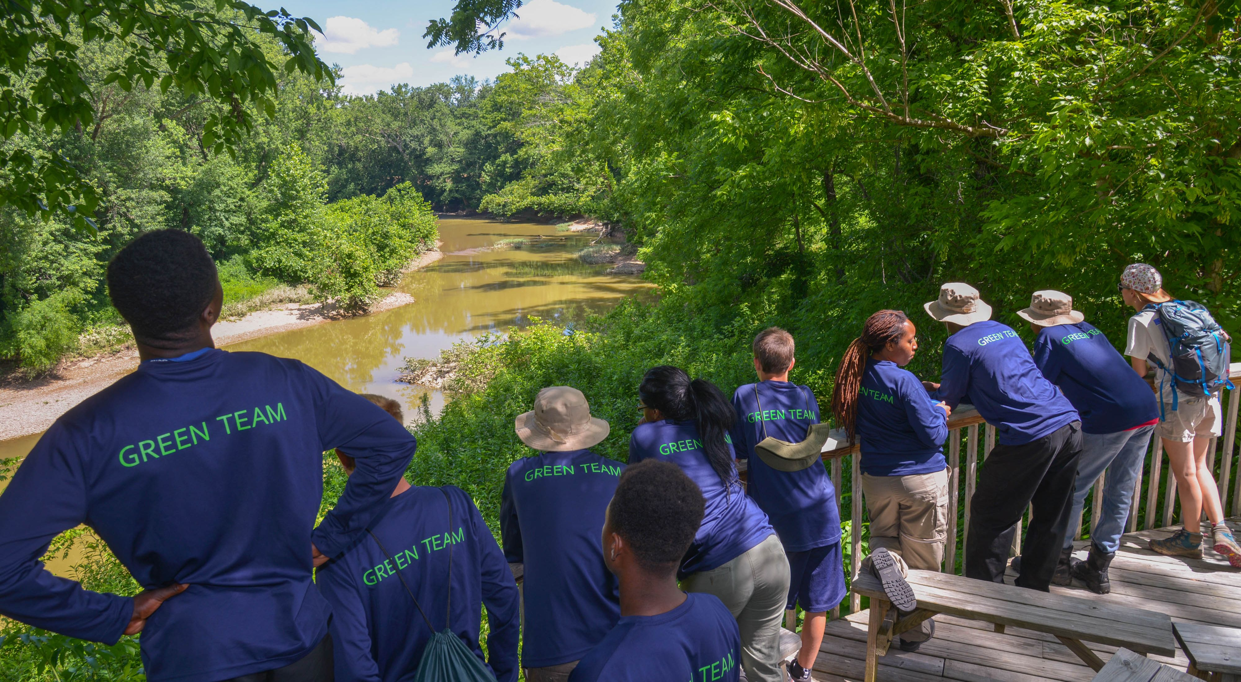 A row of teenagers in matching blue shirts stand along a wooden rail overlooking a river, surrounded by lush, green leaves.