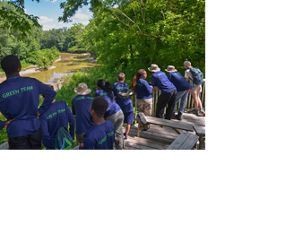 A group of teenagers wearing matching blue t-shirts, lined up along a wooden deck, overlooking a river in the summer.
