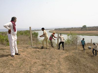 Community members fencing off a portion of the riverbank to prepare for sapling plantation during the monsoon.