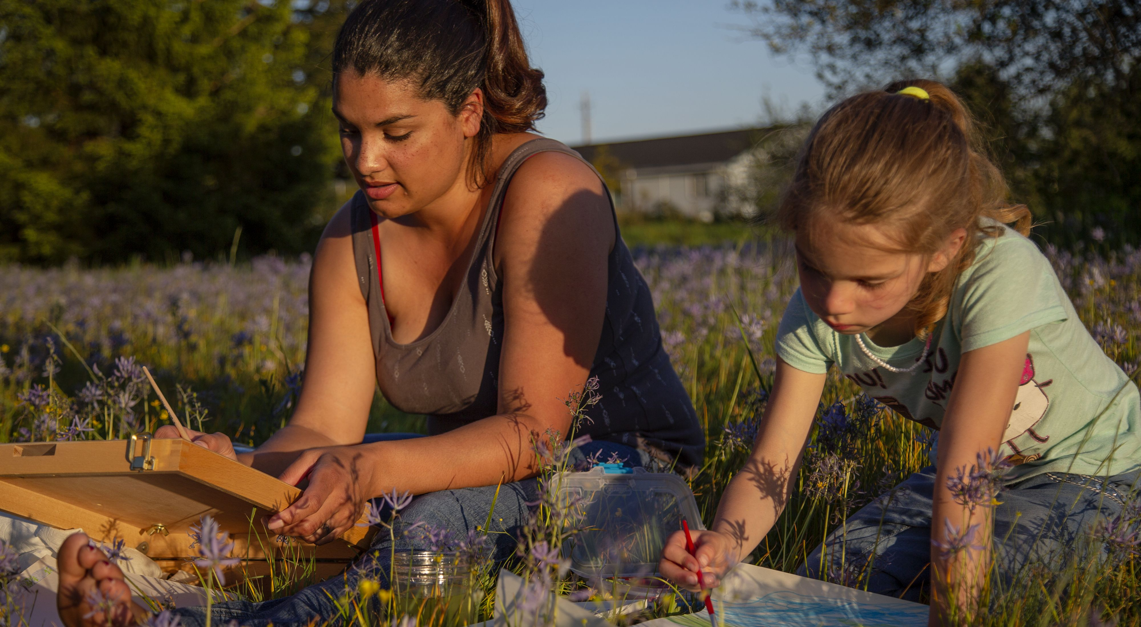 Kenison sits beside daughter-hair in ponytail-in a field of high purple meadow flowers, each with a canvas and paintbrush. Both focused on painting. House sits in distance.