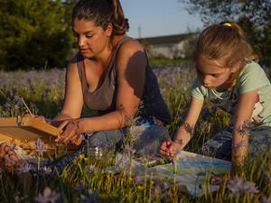 Kenison beside 6-year-old girl paint in field of flower
