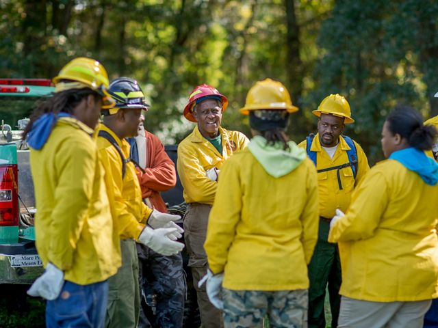 A group of Job Corps fire training students gather to listen to instructors