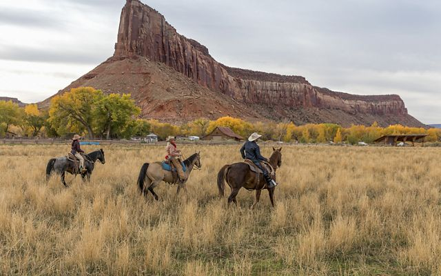 Three people in jeans and western hats ride horses in high grass. A red rock formation juts sharply upward in the distance.
