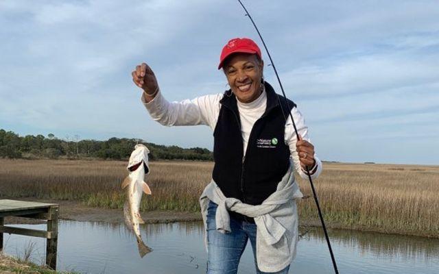 Dale Threatt-Taylor sostiene una caña de pescar en una mano y de su otra mano cuelga un pez capturado.