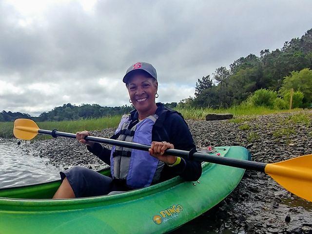 Dale Threatt-Taylor sostiene un remo dentro de un kayak, en una orilla frente a un paisaje boscoso.