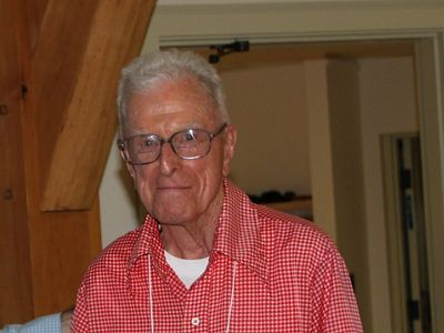 A older man wearing glasses and a red checkered shirt.