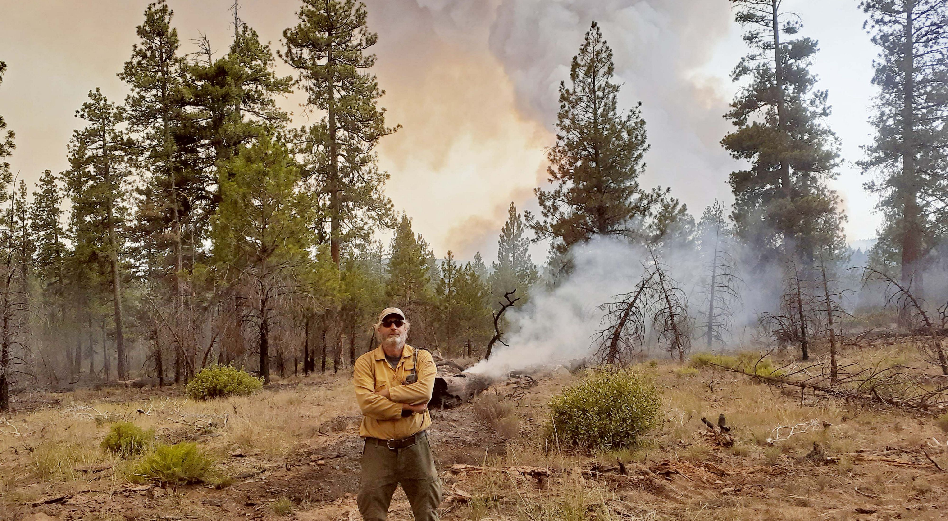 David Printiss stands on the Sycan Marsh Preserve as smoke from the Bootleg Fire billows in the background.