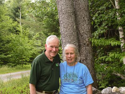 A man and woman standing in front of woods.