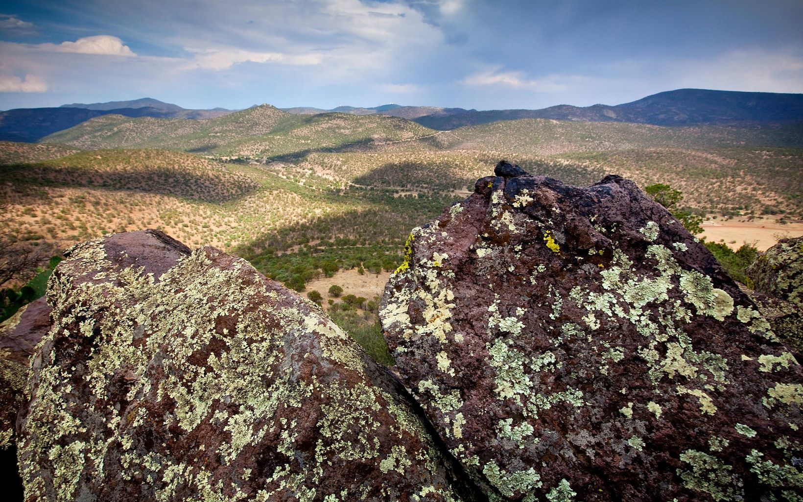Lichen-covered rocks in the foreground and a view across broad, low hills and mountains.