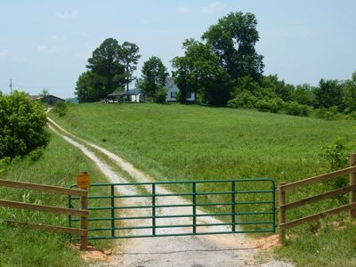 A dirt road leads to a farm house.