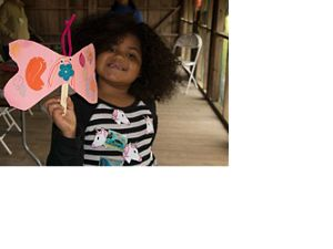 A little girl holds up a pink butterfly made of construction paper.