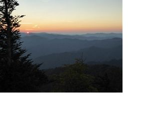 The sun sets over a forested valley.
