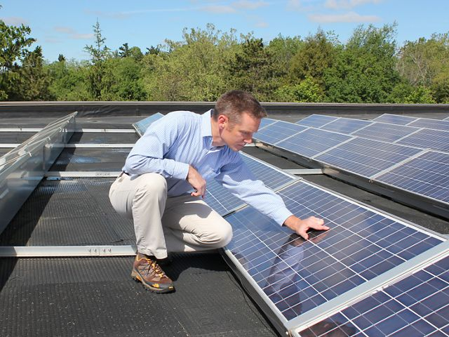 A man inspects solar panels on top of a roof.