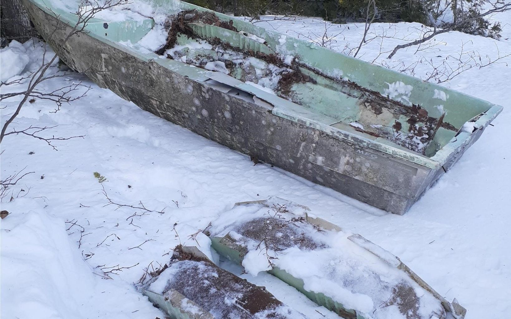 The remains of an old rotting boat lie in the snow.