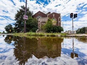 A church facade is reflected in a flooded city street.