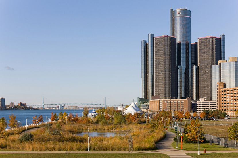 A park with a retention pond and walking path next to the Detroit River in the foreground, with the Renaissance Center in the background.