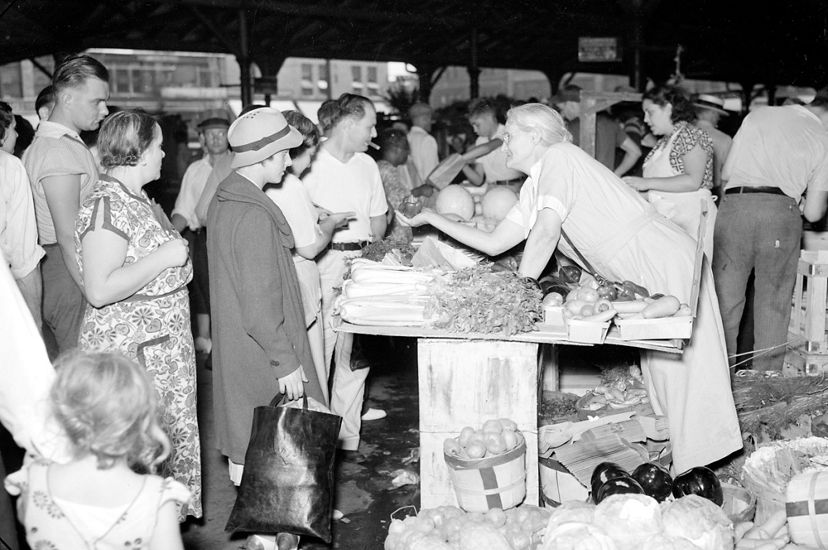 Black and white photo of a crowded market, with a vendor leaning over a table of produce for sale.