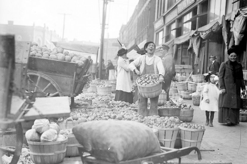 Black and white photo of a man on a sidewalk holding a large basket of apples, surrounded by more baskets at his feet.