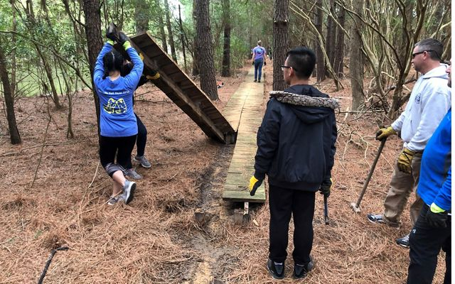 A group of college students demolish a damaged section of boardwalk.