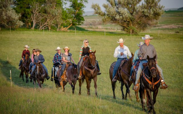 The Doan Family (ten people) on horses riding through a pasture.