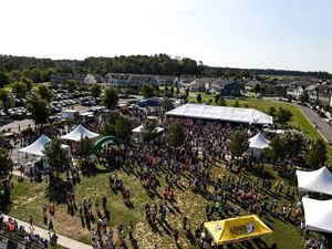 Aerial view of a large group of runners gathered for the start of a race. Several hundred people stand in a grassy area, lined up or gathered around white tents to sign in for the race.